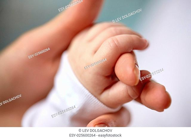 family, motherhood, parenting, people and child care concept - close up of mother and newborn baby hands
