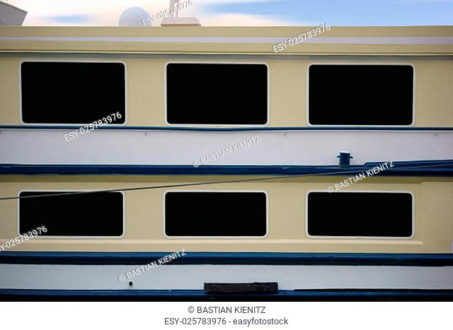 the side view of a passenger ship,starboard,with windows and railing