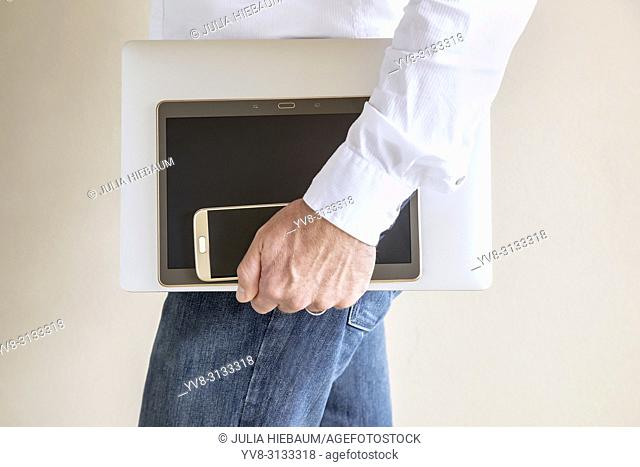 Adult male holding his laptop, ipad and cel phone