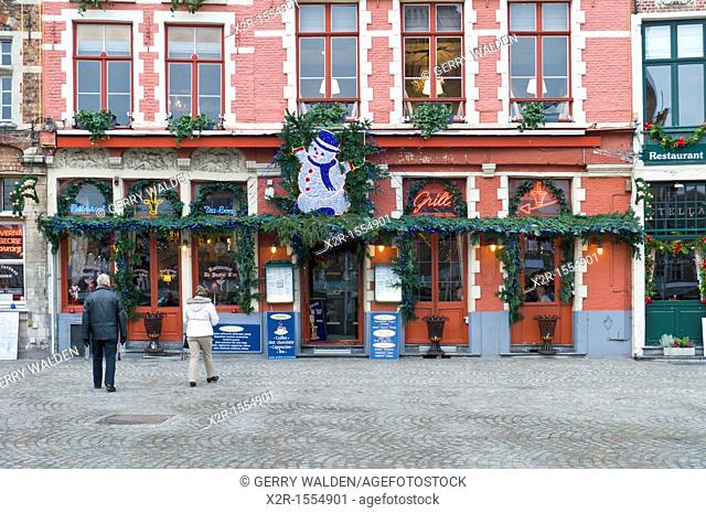 Restaurant in the centre of Brugge, Flanders, Belgium  There is a snowman over the door, and the cobbled street is shown