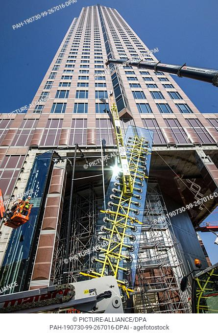 30 July 2019, Hessen, Frankfurt/Main: Workers and a crane are busy assembling the first new glass elements in the base area of the Messeturm
