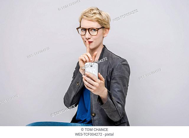 Portrait of blond woman with finger on her mouth in front of grey background