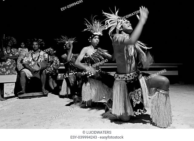Polynesian Pacific Island Tahitian male dancers in costume dancing on tropical beach. (BW)
