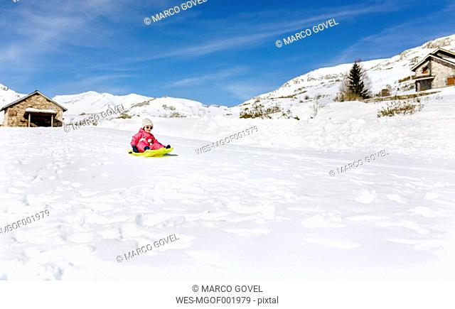 Spain, Asturias, girl with sledge in the snow, sledging