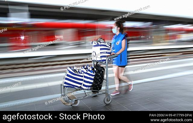 03 June 2020, Saxony-Anhalt, Magdeburg: Student Cinthia Lehn walks with a luggage cart full of clothing donations for the Ecumenical Station Mission over track...