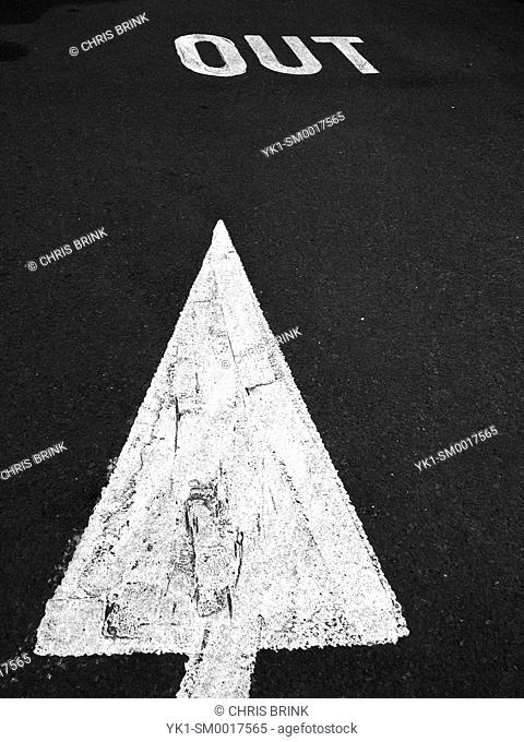 Painted arrow on tarmac pointing to out sign