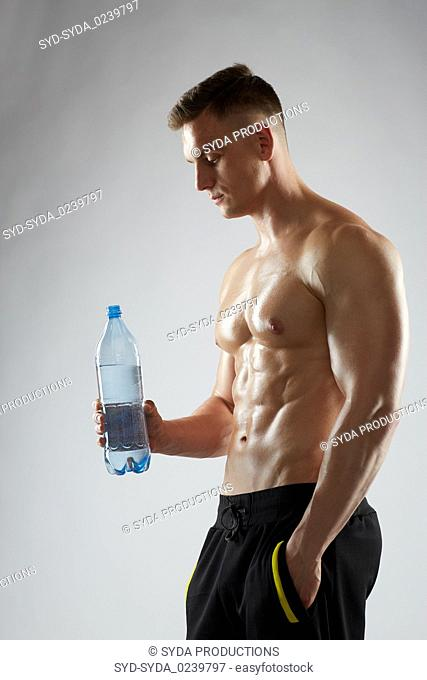 young man or bodybuilder with bottle of water