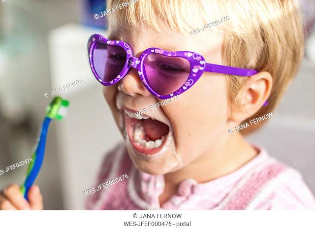 Portrait of little girl wearing sunglasses brushing teeth