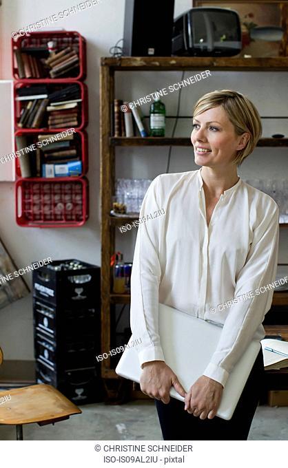 Mid adult woman holding laptop, portrait