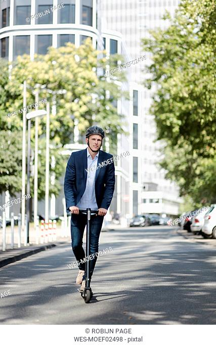Young businessman riding e-scooter in the city