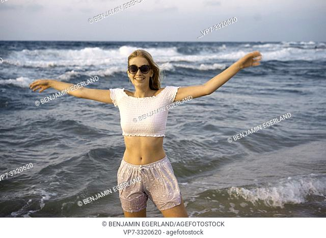 young carefree woman enjoying holiday at beach, open arms, in Crete, Greece
