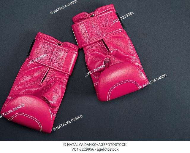 new pink sport leather boxing gloves on a black background, top view