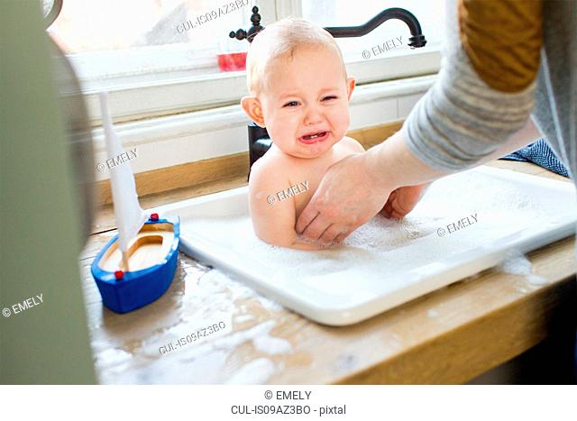 Mother removing upset baby son from kitchen sink