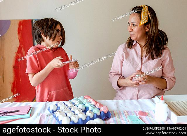 Mom and son talking while making egg art project