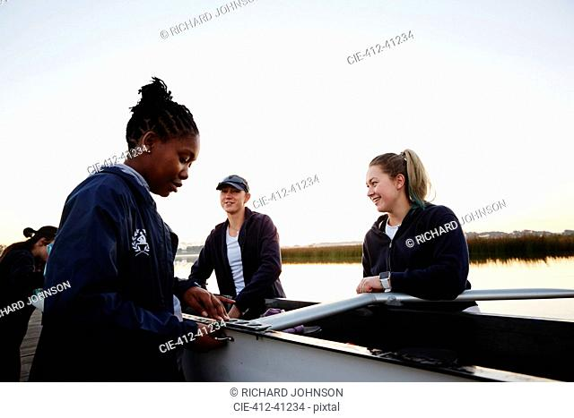Female rowers preparing scull