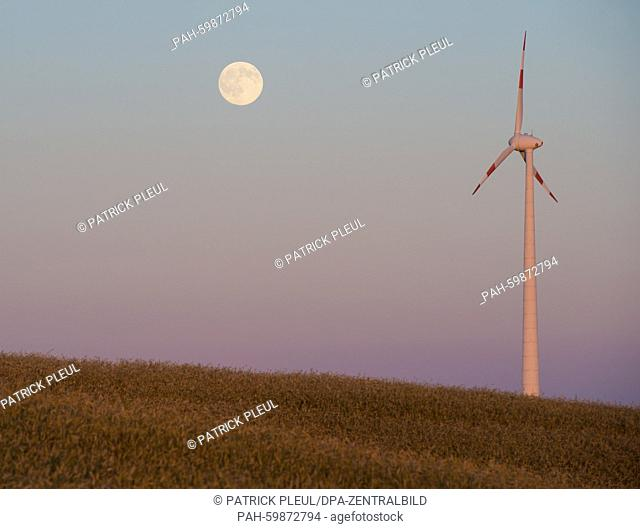 The waxing moon, visible for 98 % according to the moon calander, above a grain field and a wind turbine near Mallnow (Brandenburg), Germany, 01 July 2015