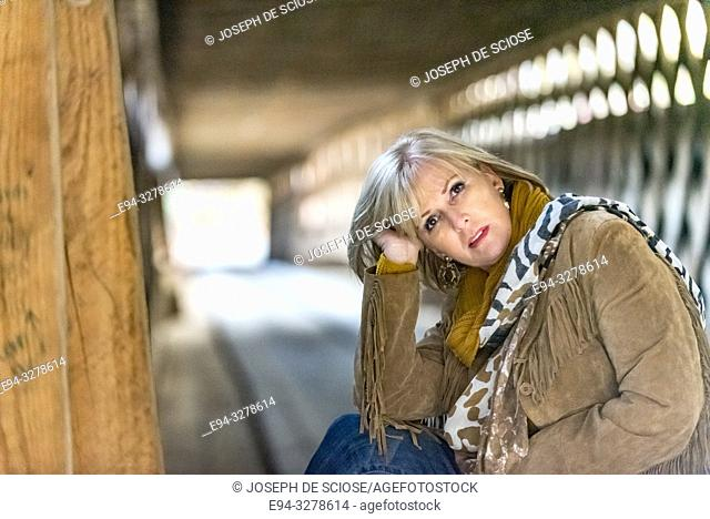 A pretty 59 year old blond woman looking directly at the camera sitting in the middle of a covered bridge, Alabama