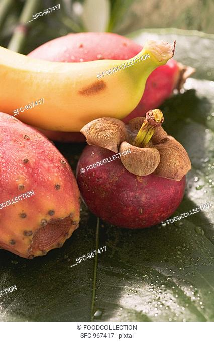 Mangosteen, prickly pears and banana on leaf