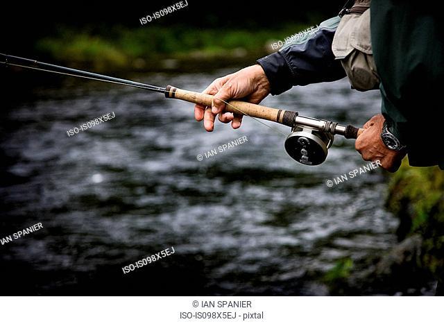 Casting fishing rod in Margaree River, Cape Breton Island, Nova Scotia