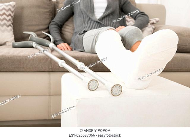 Close-up Of Woman With Plastered Leg Sitting On Couch At Home