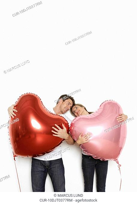 Young couple holding huge heart shaped balloons and looking at each other lovingly