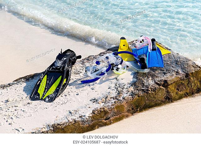 diving, snorkeling, leisure and summer vacations concept - scubas, masks and flippers on beach