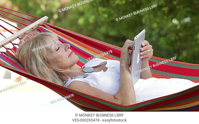 Senior woman rocking in hammock using digital tablet. Shot on Canon 5d Mk2 with a frame rate of 30fps