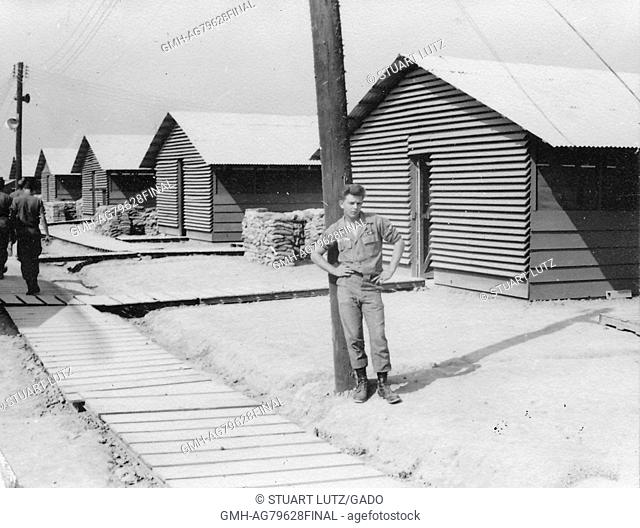 A United States Army serviceman in uniform leaning against a utility pole with his hands on his hips, pallets form the walkway that other soldiers are using to...
