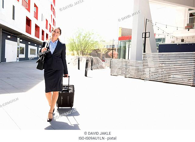 Mid adult businesswoman, pulling suitcase, outdoors