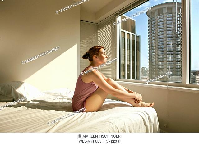 Woman sitting on bed looking out of window
