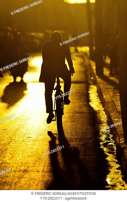 Man riding bicycle on street during sunset,Santa Clara, Cuba