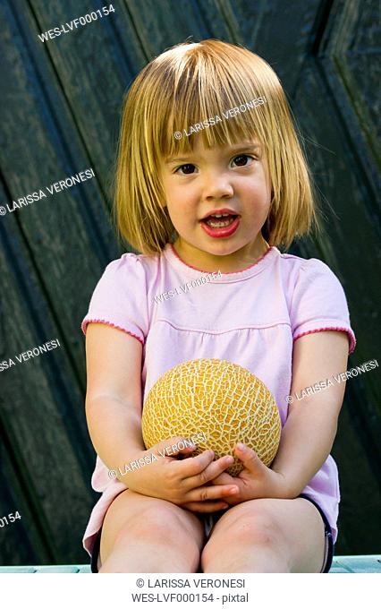 Germany, Bavaria, Portrait of girl holding galia melon, close up