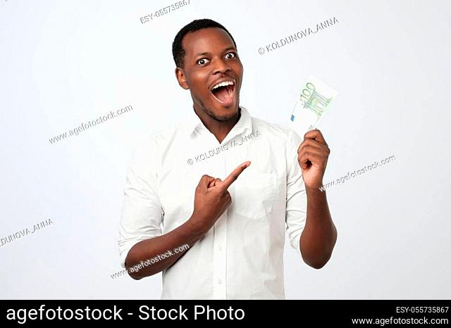 Afro american man holding hundred euro. He is very happy pointing with hand and finger. Great investment concept, receive a profit