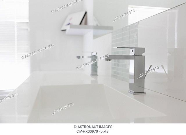 Modern white bathroom sink and faucet in home showcase interior