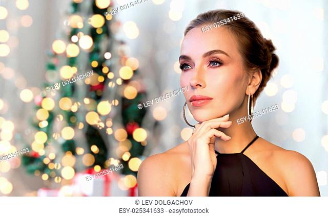 christmas, people, luxury, jewelry and fashion concept - beautiful woman in black wearing diamond earring and ring over holidays lights background