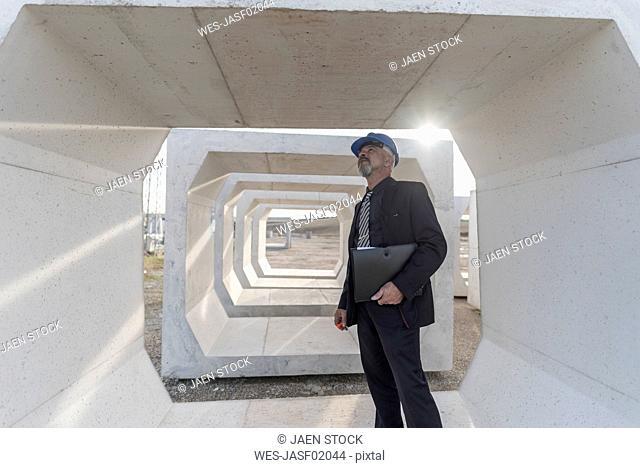 Businessman examining concrete block on industrial site