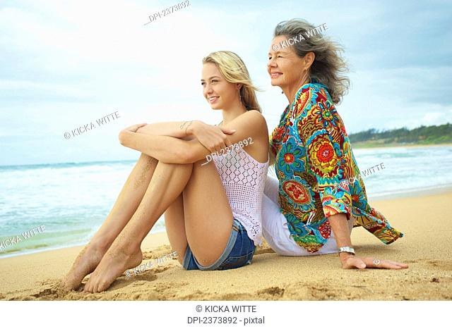 A mother and daughter sitting together on the beach at the water's edge; Kauai, Hawaii, United States of America