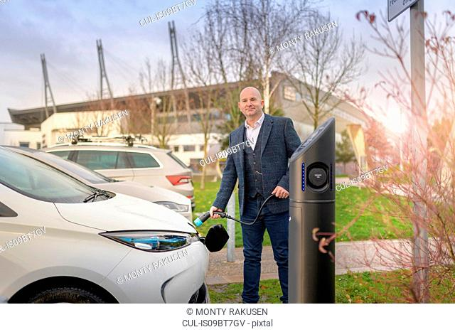 Portrait of businessman plugging in electric car at charging point, Manchester, UK