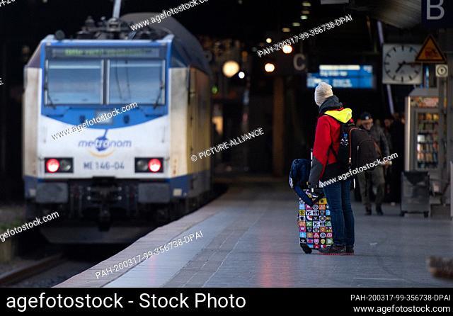 17 March 2020, Hamburg: A traveller is standing at a platform in the main station in Hamburg. Photo: Daniel Reinhardt/dpa. - Hamburg/Hamburg/Germany
