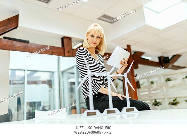 Businesswoman in office looking at models of wind turbines