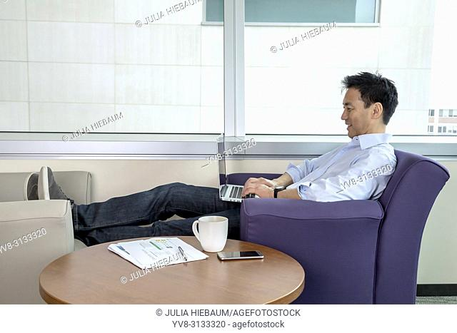 Adult Asian man working on his laptop
