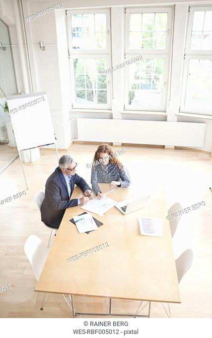 Businessman and woman in boardroom