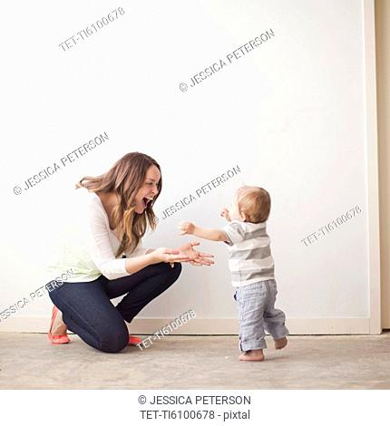 Young mother assisting baby boy 6-11 months in first steps