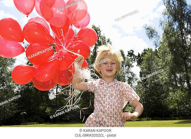 Boy holding bunch of red balloons