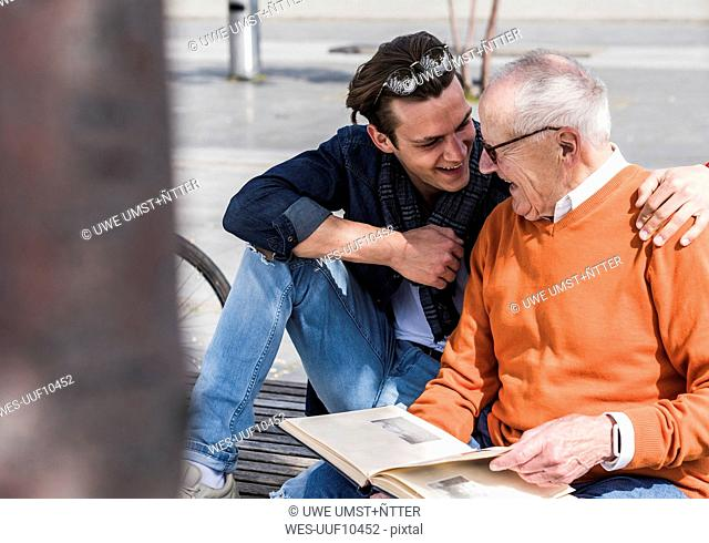 Happy senior man and adult grandson with photo album outdoors