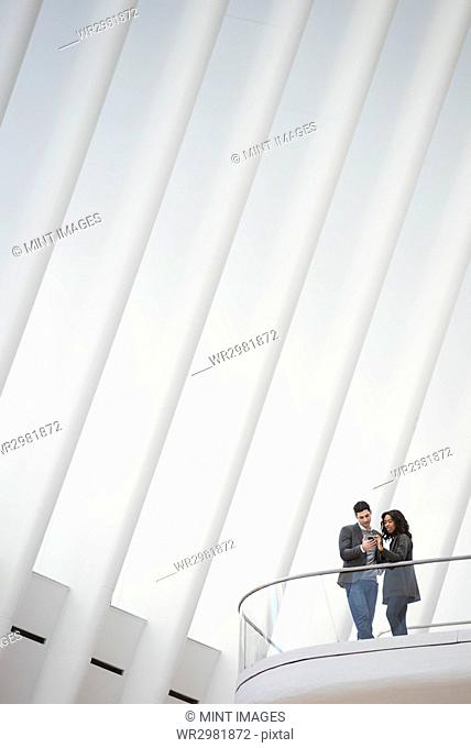 View from below of two people standing on a balcony in the Oculus building, floating balconies above the ground in the roof space