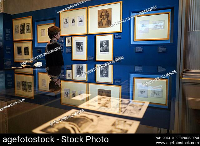 """10 March 2020, Berlin: There's a woman in the exhibition """"""""This kiss of the whole world!"""""""" - The Beethoven Collection of the Berlin State Library"""""""" in front of..."""