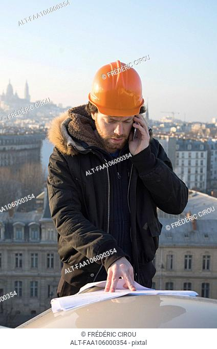 Construction supervisor talking on cell phone and looking at blueprints