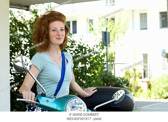 Portrait of redheaded young woman with motor scooter