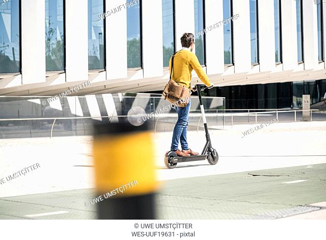 Young man riding e-scooter in the city
